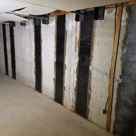 What are carbon straps and why are they important in a basement renovation project?